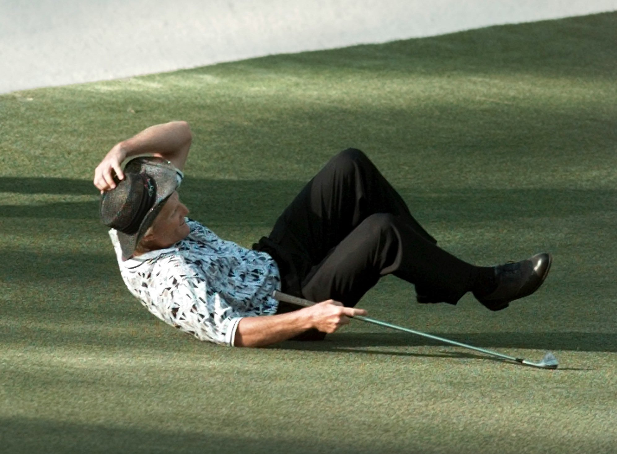 Greg Norman falls to the ground after missing his shot for an eagle on the 15th hole during final round play of the 1996 Masters at the Augusta National Golf Club in Augusta, Ga., Sunday , April 14, 1996. (AP Photo/Dave Martin)